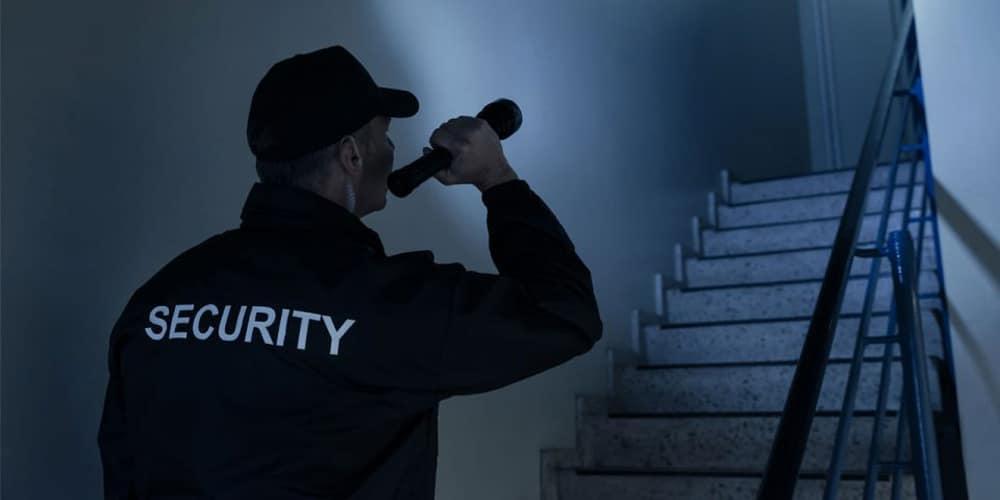 Agent de sécurité dans un escalier avec une lampe torche